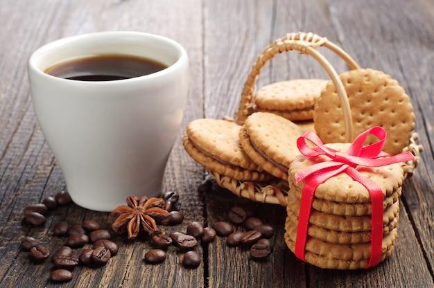 Biscoitos doces amarrados com fita e xícara de café em uma mesa de madeira