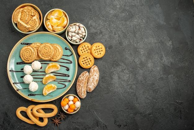 Biscoitos doces com balas e biscoitos no fundo cinza