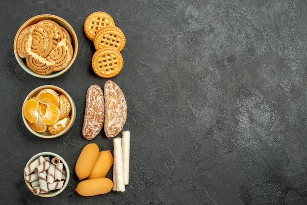 Biscoitos doces com biscoitos e frutas em fundo cinza