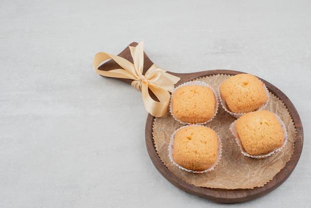 Biscoitos doces com creme na placa de madeira decorada com fita.