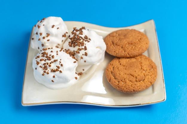 Biscoitos doces com deliciosos sorvetes dentro do prato na mesa azul