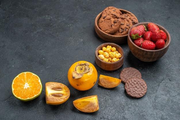 Biscoitos doces com frutas em fundo escuro de vista frontal