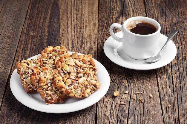 Biscoitos doces com nozes e xícara de café na velha mesa de madeira