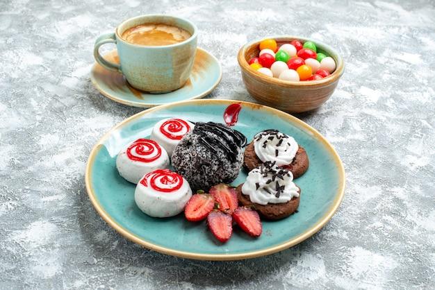 Biscoitos doces de frente com bolo de chocolate e café no espaço em branco