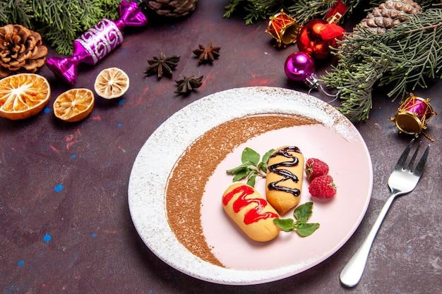Biscoitos doces de frente dentro do prato em um espaço escuro