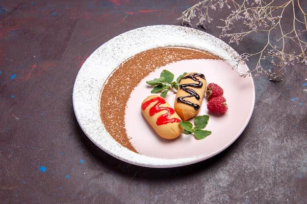 Biscoitos doces de vista frontal dentro de um prato desenhado no espaço escuro