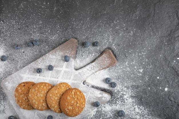 Biscoitos doces deliciosos na tábua de madeira com mirtilos