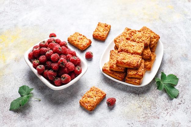 Biscoitos doces e deliciosos de geléia de framboesa com framboesas maduras, vista superior