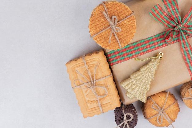 Biscoitos doces em corda com presente e brinquedo dourado de natal na mesa branca