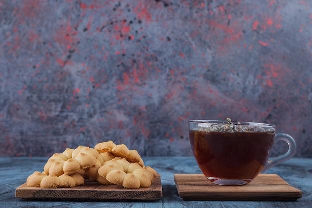 Biscoitos doces em forma de flor e copo de chá de ervas sobre fundo azul.