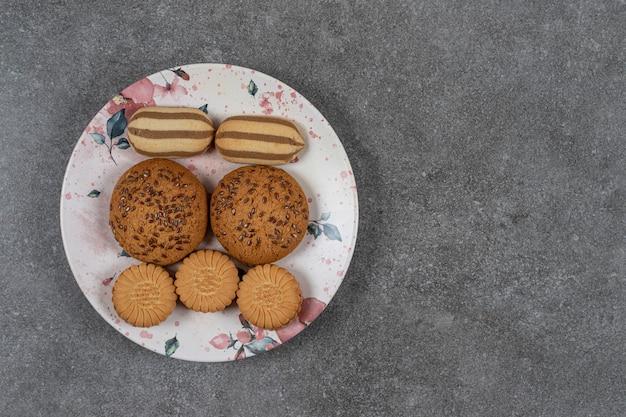 Biscoitos doces no prato na superfície do mármore