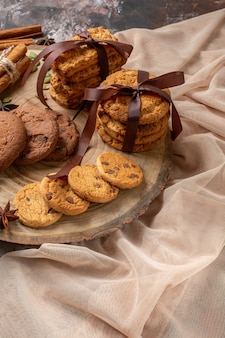 Biscoitos doces saborosos de frente com xícara de café na cor de fundo claro cacau açúcar chá bolo biscoito torta doce