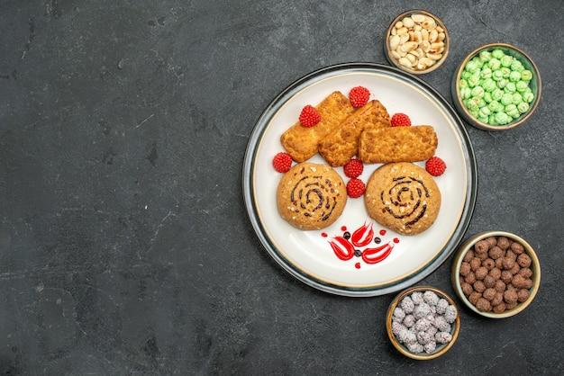 Biscoitos doces saborosos de vista de cima dentro do prato no fundo cinza biscoito doce bolo de biscoitos chá