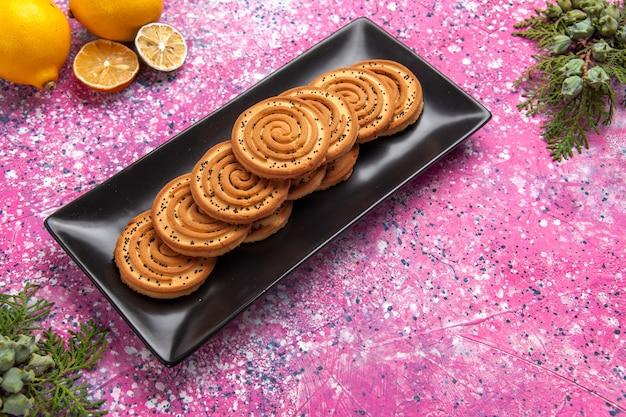 Biscoitos doces vista metade superior deliciosos biscoitos dentro de forma preta com limões na mesa rosa claro.