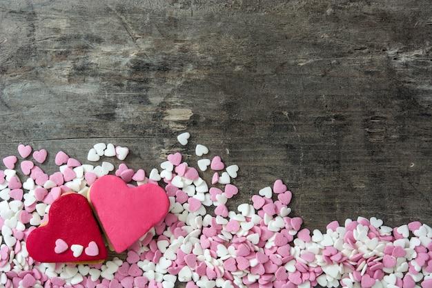 Biscoitos dos namorados com forma de coração na superfície de madeira