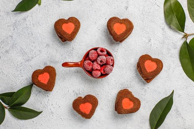 Biscoitos dos namorados com framboesas congeladas na luz em forma de coração