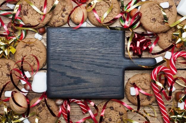 Biscoitos dos pedaços de chocolate cenário vermelho e marshmallow do ouro do caramelo dos bastões do natal em de madeira. quadro de copyspace.