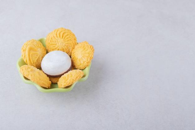 Biscoitos e biscoito glaceado em uma tigela na mesa de mármore.