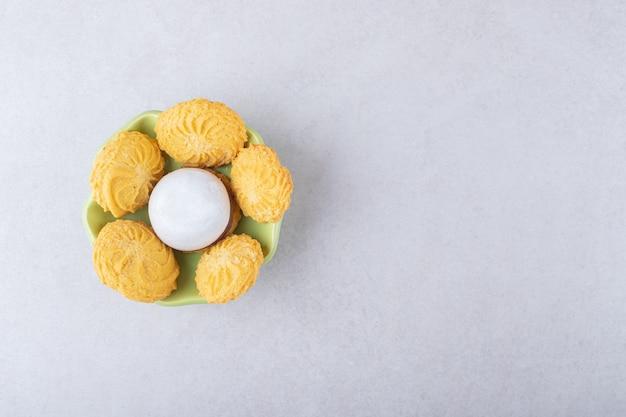 Biscoitos e biscoito glaceado em uma tigela, no mármore.