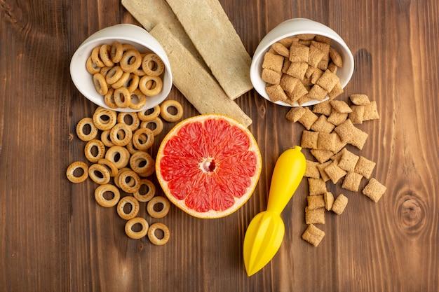 Biscoitos e biscoitos com grapefruit na mesa de madeira marrom de cima