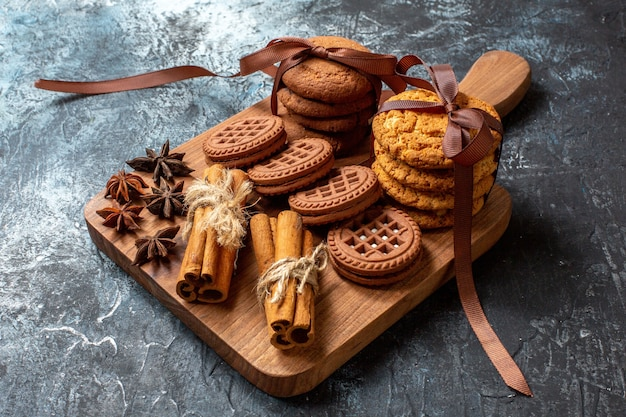 Biscoitos e biscoitos de anis em paus de canela na tábua de servir de madeira em fundo escuro.