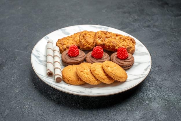Biscoitos e bolos de vista frontal dentro do prato no espaço cinza