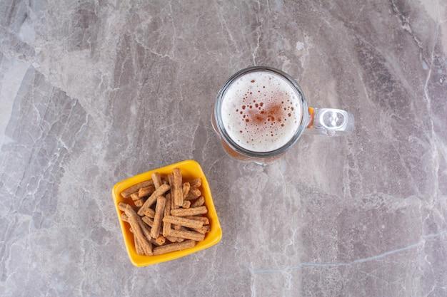 Biscoitos e copo de cerveja gelada na superfície do mármore