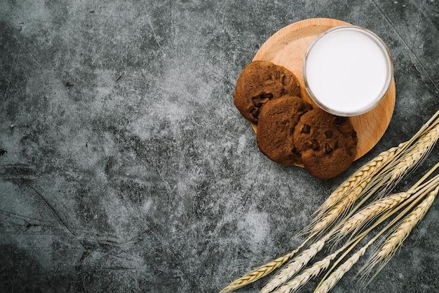 Biscoitos e copo de leite com espigas de trigo no fundo de concreto manchado