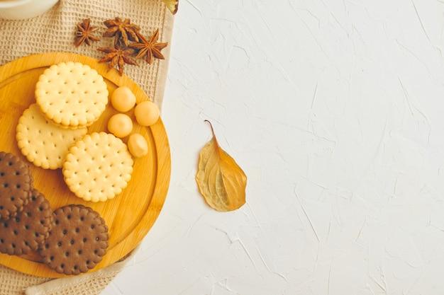 Biscoitos e doces na mesa branca de bandeja de madeira com doces de toalha de mesa de cozinha e leo de outono de anis estrelado.