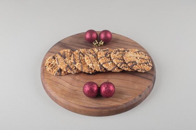 Biscoitos e enfeites de natal em uma placa de madeira em fundo branco.