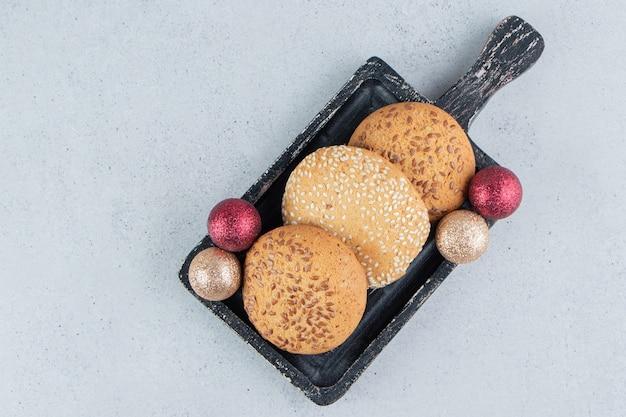 Biscoitos e enfeites em uma pequena bandeja no fundo de mármore.
