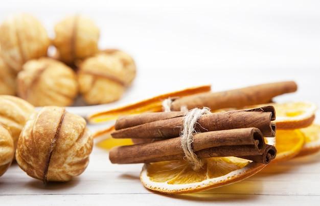 Biscoitos e fatias de laranja com canela em um fundo claro de madeira