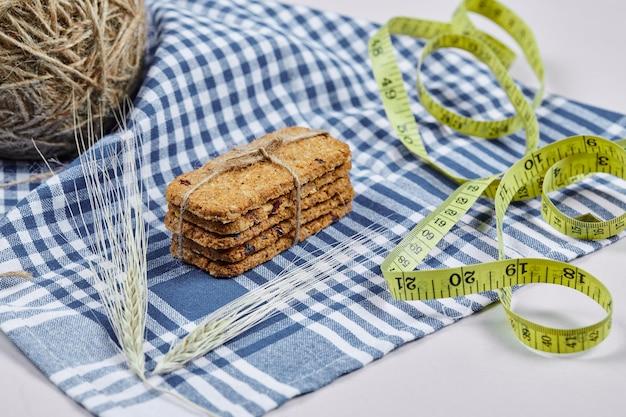 Biscoitos e fita métrica em branco com toalha de mesa, close-up.