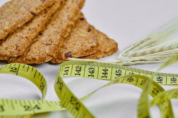 Biscoitos e fita métrica em branco.