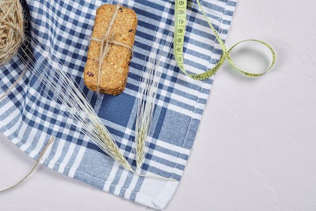 Biscoitos e fita métrica em um fundo branco com toalha de mesa. foto de alta qualidade