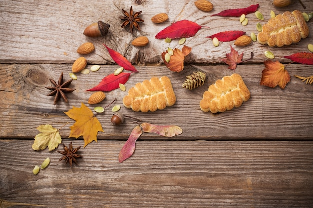 Biscoitos e folhas de outono em fundo de madeira