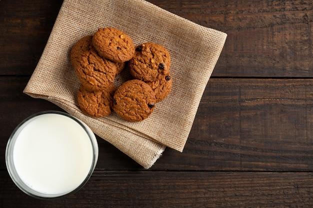 Biscoitos e leite de vidro na mesa de madeira.