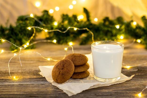 Biscoitos e leite em copo para o papai noel em frente a um bokeh de luz de natal