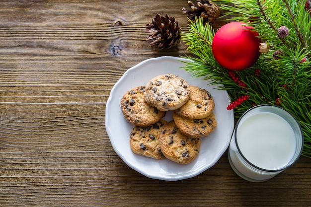 Biscoitos e leite para o papai noel em fundo de madeira
