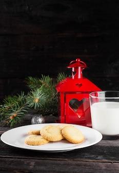 Biscoitos e leite para o papai noel em uma superfície escura. tonificação