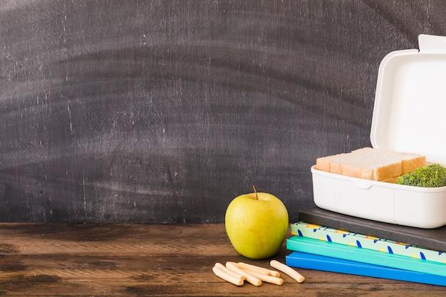 Biscoitos e maçã perto de cadernos e lancheira