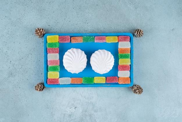 Biscoitos e marmeladas em uma bandeja azul no mármore.