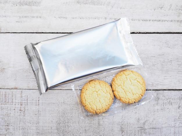 Biscoitos e pacote de folha em madeira fundo