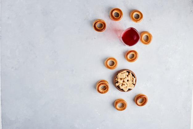 Biscoitos e pães servidos com um copo de suco, vista de cima.