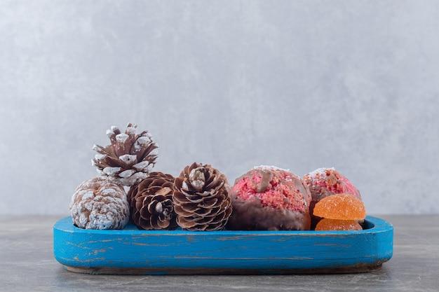 Biscoitos e pinhas em uma travessa azul na superfície de mármore