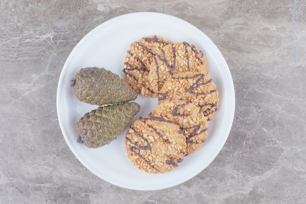 Biscoitos e pinhas numa travessa sobre mármore