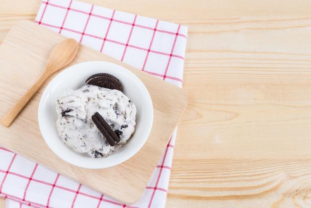 Biscoitos e sorvete de creme na mesa de madeira e guardanapo branco com colher