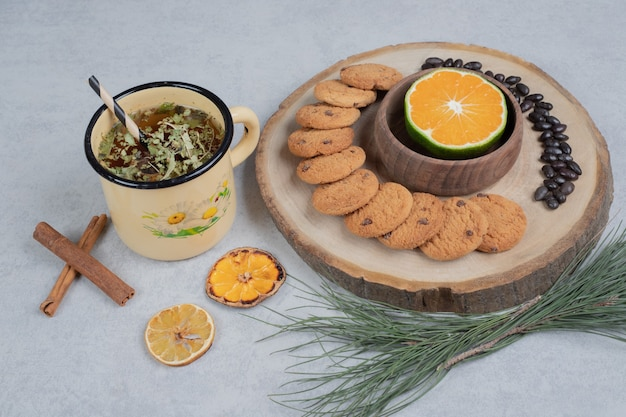 Biscoitos e uma fatia de tangerina na placa de madeira com uma xícara de chá. foto de alta qualidade