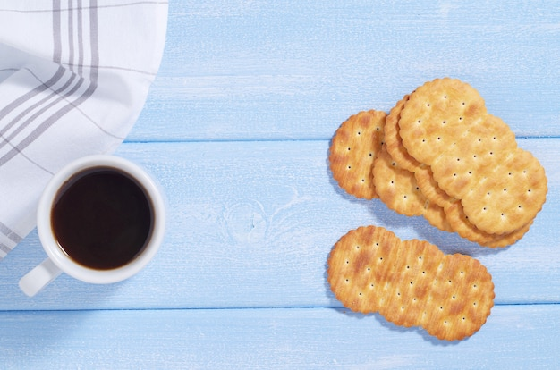 Biscoitos e xícara de café no café da manhã na mesa azul, vista de cima