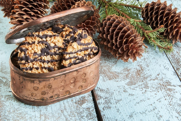 Biscoitos em caixa de cobre e galhos de árvores de natal